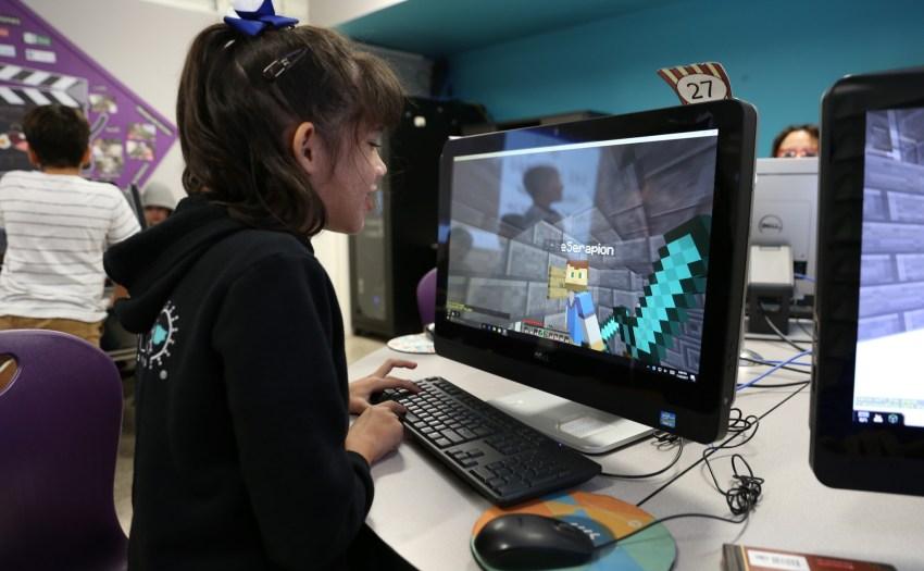 Niña sentada en un acomputadora jugando Minecraft Education Edition
