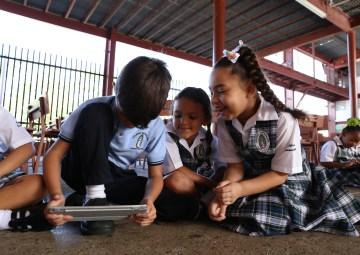 Estudiantes de primaria utilizando una tablet para potencial el pensamiento computacional