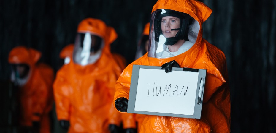 """A scientist in orange protective suit holds a sign saying """"human"""""""