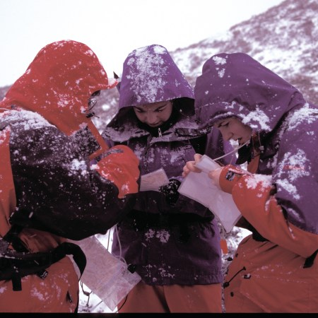 Hill walkers huddle round a map on a snowy day