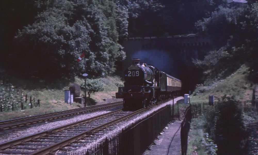 A steam train emerges from St Annes Park Tunnel in the early 1960's. Footpath leading to Nightingale Valley leads of to the right.