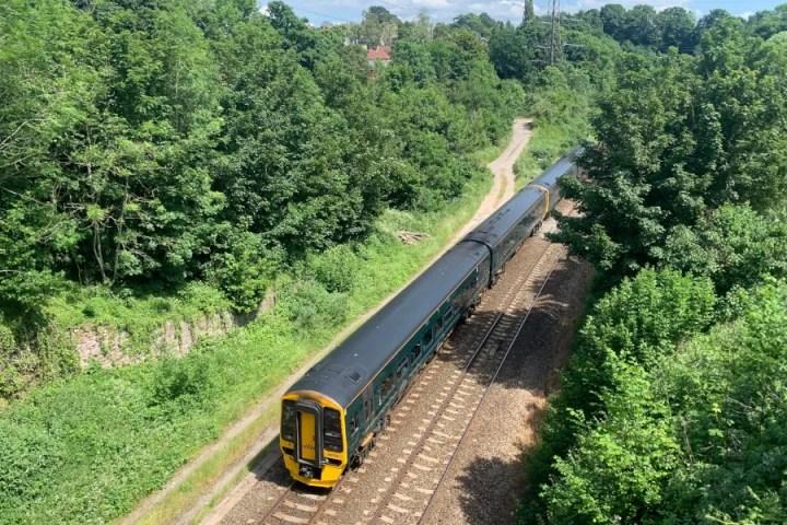 A train passes the site of St Annes Park station, June 2021