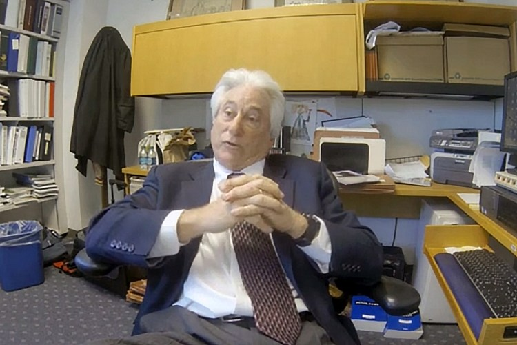 Judge Nash sitting at his office desk with hands folded in front of chest.