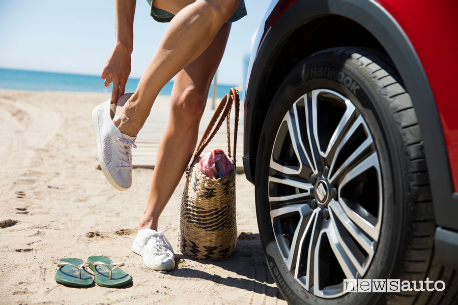 Wheel tire with sea background on the sand, flip flops, bag and comfortable shoes which are better than slippers when you drive the car.