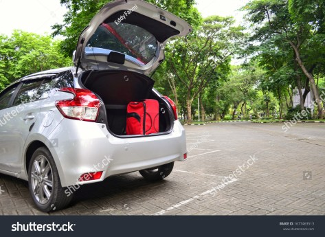red luggage in hatchback car trunk