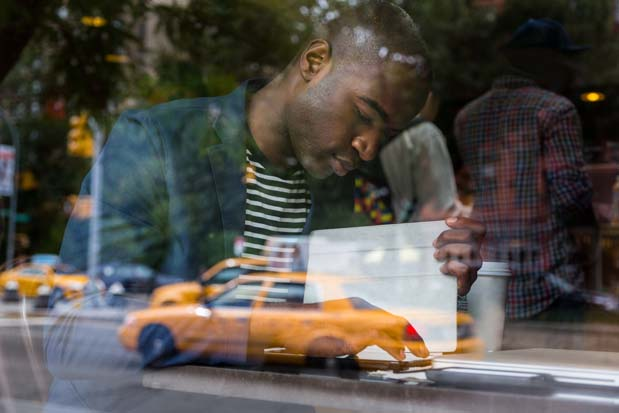 Young Black Man with Digital Tablet in a Cafe
