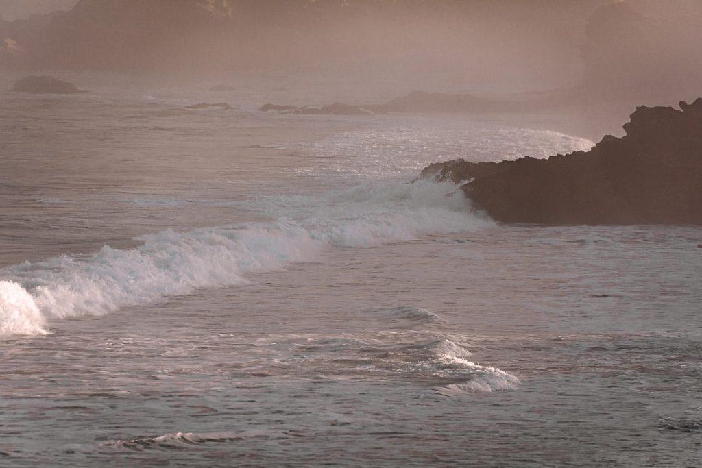 Meeresbrandung im Gegenlicht mit schroffen Felsen im Hintergrund – Sines Portugal