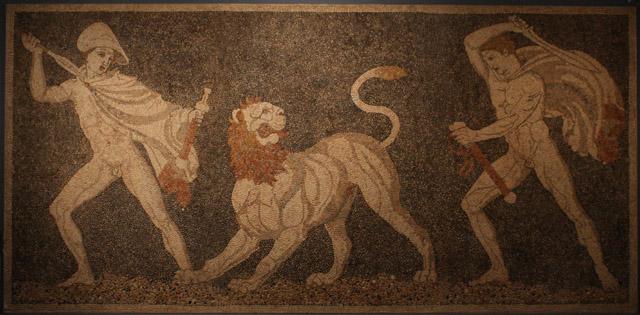 Polowanie na lwa. Prawdopodobnie po lewej przedstawiony jest Aleksander (sposób ukazania twarzy przypomina znane wizerunki rzeźbiarskie władcy) w stroju macedońskim, po prawej Krateros.