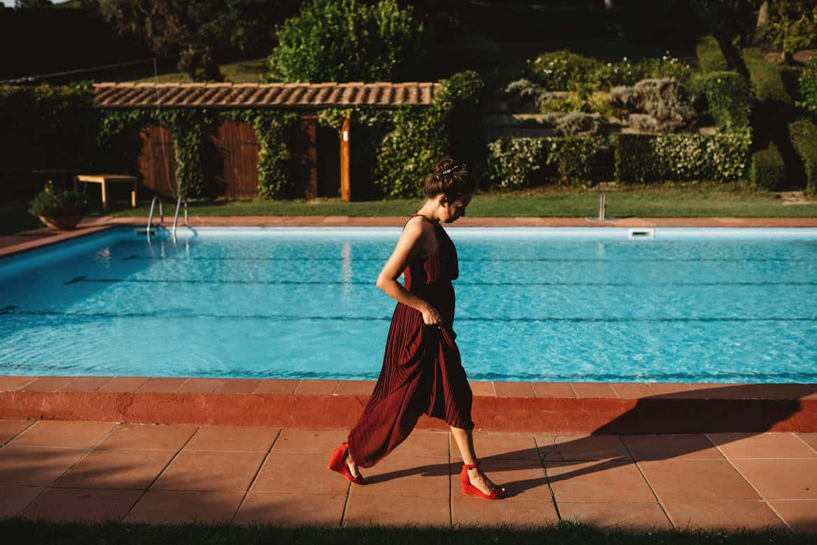 bridesmaid walking by the pool at villa di ulignano wedding