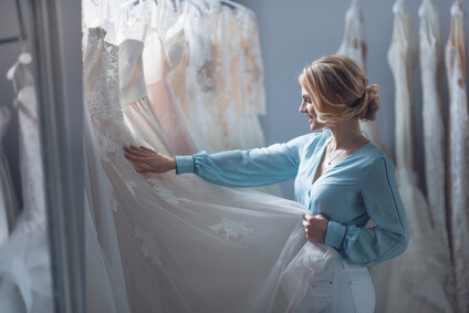 Young woman choosing a wedding dress in the store