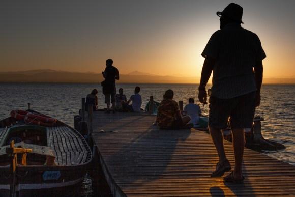 pescador va hacia su barca en Parque de la Albufera durante la puesta de sol (Valencia)