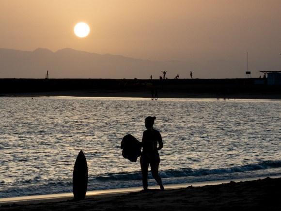 chica pasea por playa en Tenerife durante la puesta de sol