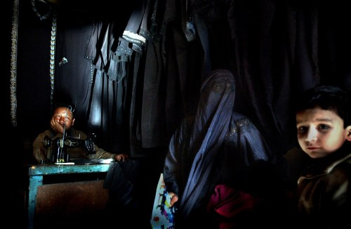 "A Muslim Kashmiri woman sits inside a shop with her children where traditional Islamic veils are made, March 26, 2002 in Srinagar, the summer capital of Indian held Kashmir. The shadowy group, Lashkar-e-Jabbar, also known as Allah's Army sent a letter to a local newspaper saying that Muslim Kashmiri women must adhere to the dress code or face acid attacks beginning on April 1, 2002. The leader of the group also wrote, ""if our members see any boy or girl or any illegal couple doing acts of immortality they will be killed there and then"".The same group claimed responisiblity for two acid attacks on women in Srinagar last year. Kashmir has been the center of the ongoing dispute between India and Pakistan since the region was partioned when the British left in 1947.(Ami Vitale/Getty Images)"