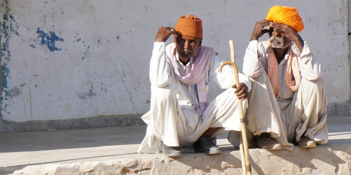 Rajasthan: zwei ältere Herren hocken auf einem Mauerabsatz