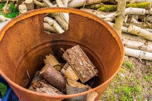 Rostige Tonne mit Feuerholz