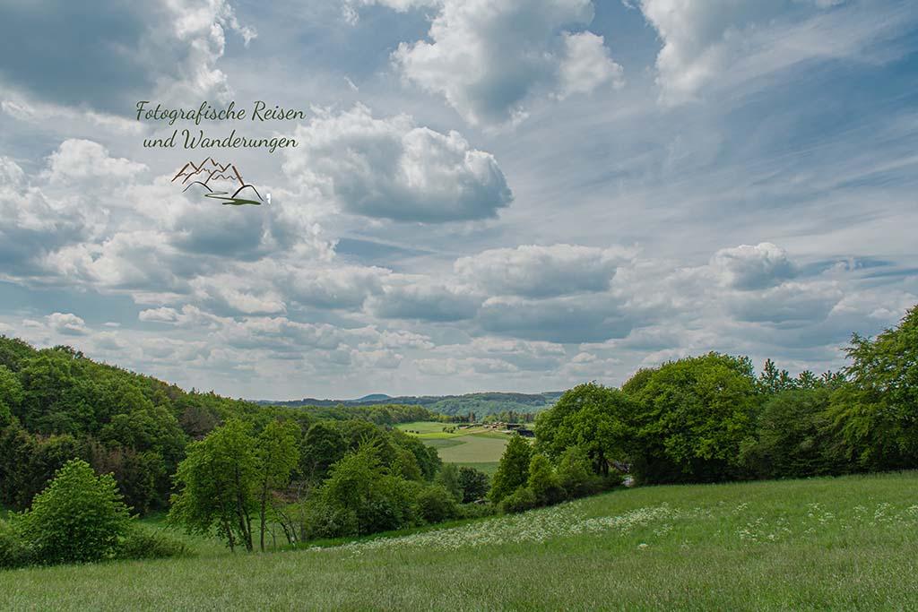 Sommerlandschaft mit dicker Wolkenschicht am Himmel - Abenteuer Wanderung im Sahrbachtal