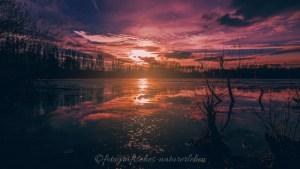 gefrorener See mit rotem Sonnenuntergang und Spiegelung