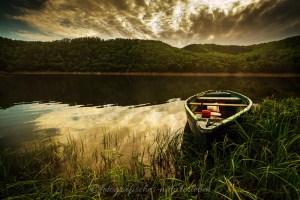Edersee mit Holzboot und Wolkenspiel, klares Wasser