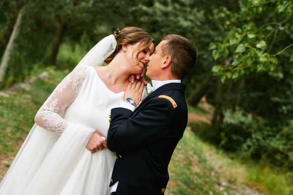Pareja de recién casados besándose en le campo.