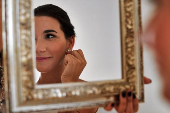 Novia dándose los últimos detalles con la colocación de los pendientes delante del espejo