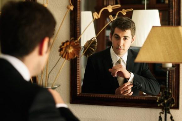 Novio dándose los últimos detalles delante del espejo.