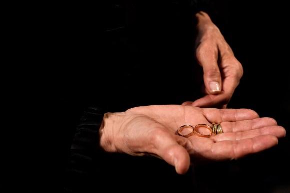 Madrina luciendo los anillos de los novios en su mano