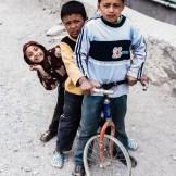 Niños nepalís compartiendo una bicicleta con las ruedas sin cámaras. - Jomsom, Mustang, Nepal.