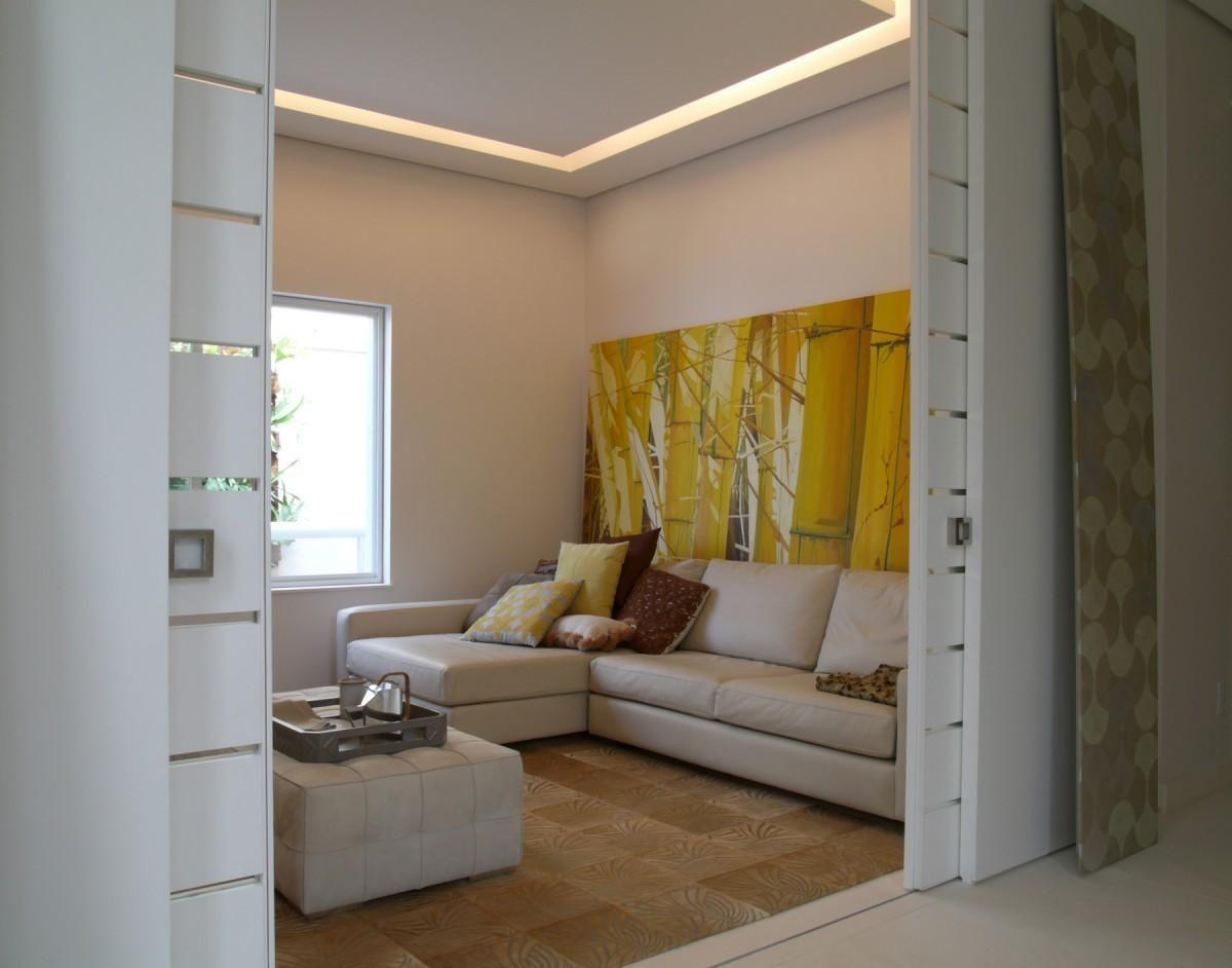 Quadro grande amarelo na sala de estar de Denise Barretto