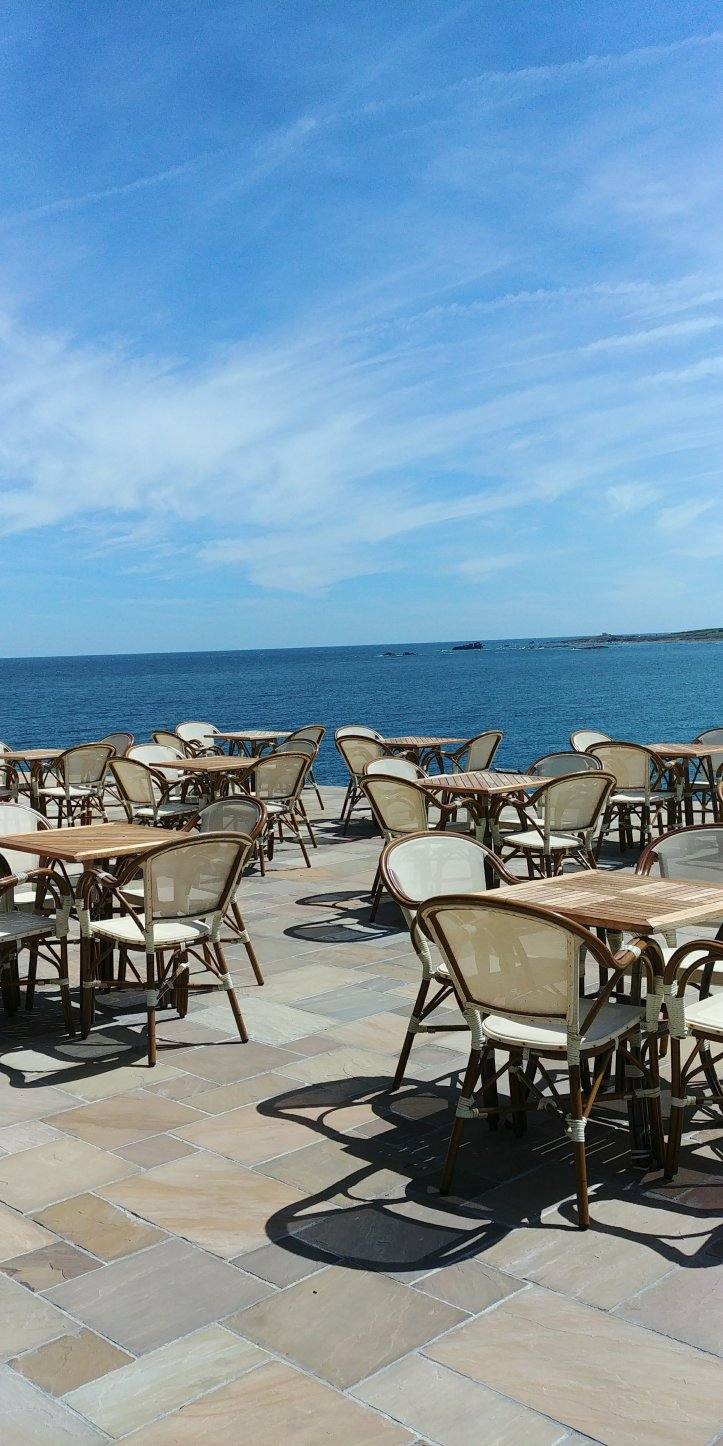 Empty seats at a closed restautant with beautiful view over the sea, Normandie, France