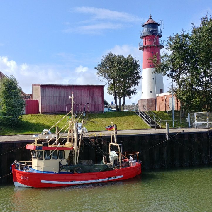 Büsum, little red boat and lighthouse, photo by fotosbykarin