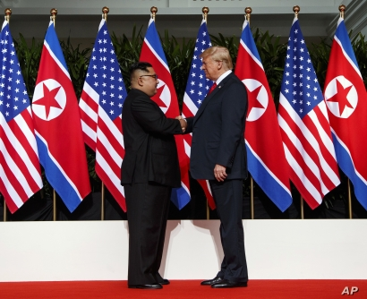 FILE - Kim Jong Un and President Donald Trump shake hands prior to their meeting in Singapore, June 12, 2018.