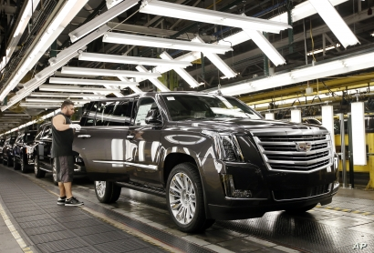 FILE - An employee inspects a Cadillac Escalade as it nears the final process of assembly at the General Motors plant in Arlington, Texas, July 14, 2015.