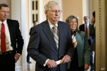 In this Oct. 29, 2019, photo, Senate Majority Leader Mitch McConnell of Ky., center, walks to the podium with Sen. John…