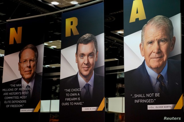 Images of NRA CEO Wayne LaPierre, Legislative Director Chris Cox and President Oliver North displayed during the National Rifle…