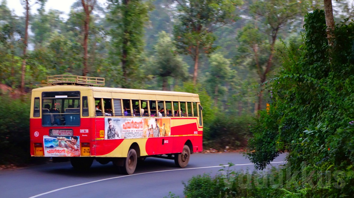 A KSRTC fast passenger bus rounds a corner at high speed on KK Road near Kumily