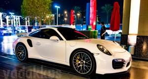 a white Porsche 911 at the Dubai Mall at night