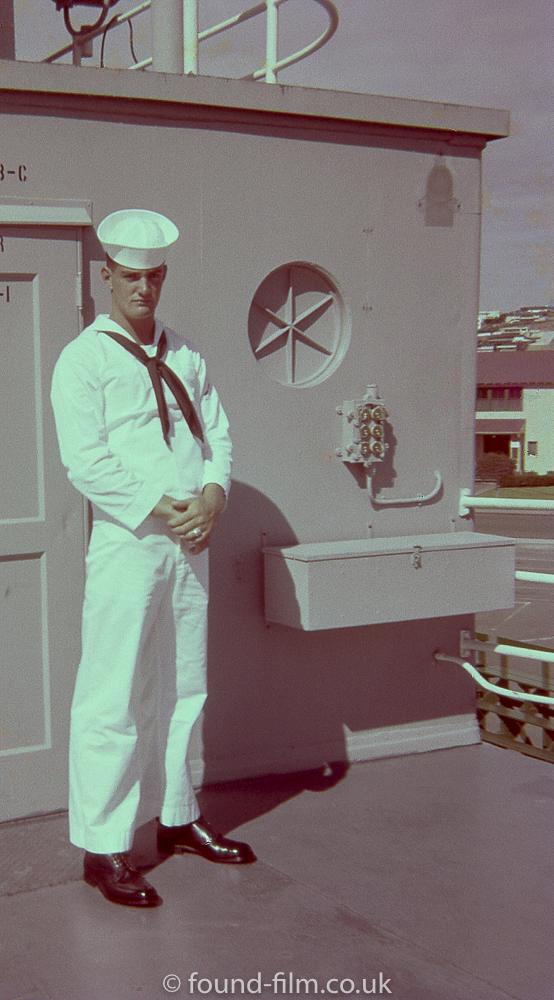 Sailor standing by a door on the deck of the ship