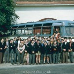 Schoolboys posing by a coach