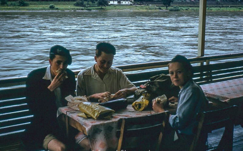 Three children having lunch by the river