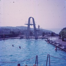 A diver on a diving board above a swimming pool