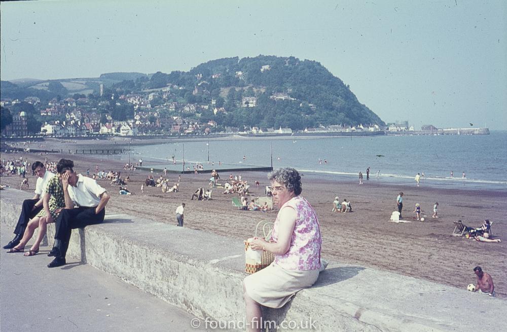 Lady sitting on the seawall at Minehead beach