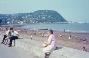 Lady sitting on the seawall ant Minehead beach