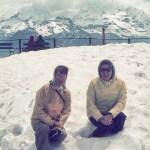 Two women sitting in snow