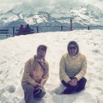 Two women sitting in snow