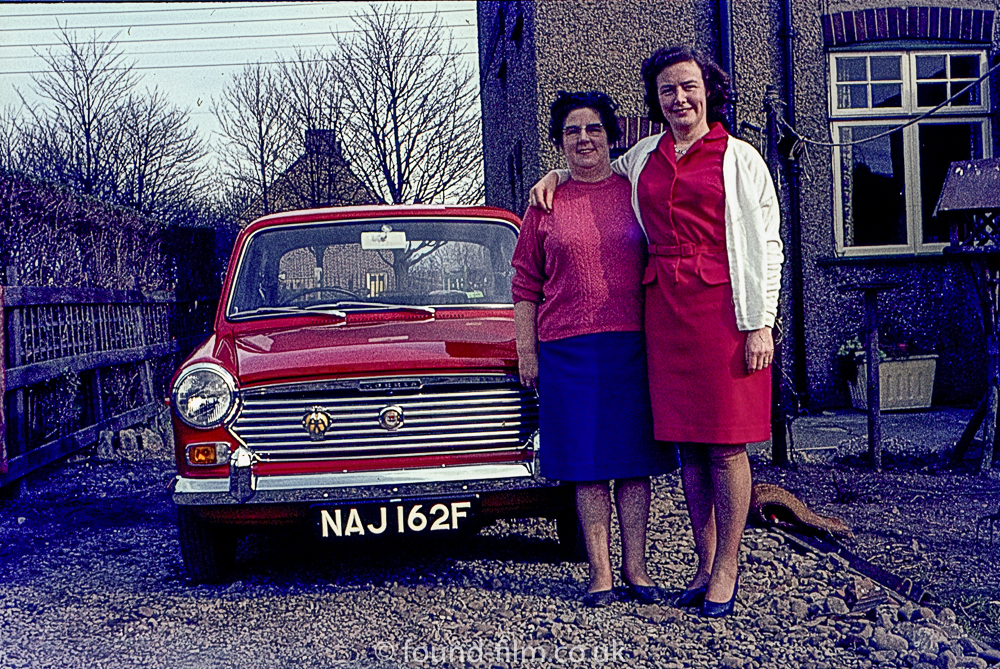 Two women and their red Austin 1100 car