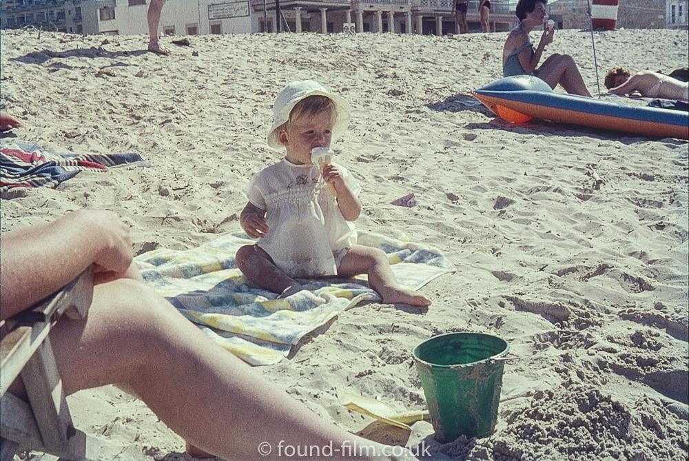 Baby on a beach eating an ice-cream