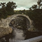 Arched stone footbridge over a stream.