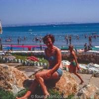 Woman sitting on a rock in a bikini in August 1969
