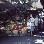 Woman buying fruit and veg from a market scene in May 1980