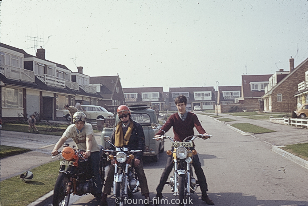Men sitting on motorbikes in a housing estate, August 1972